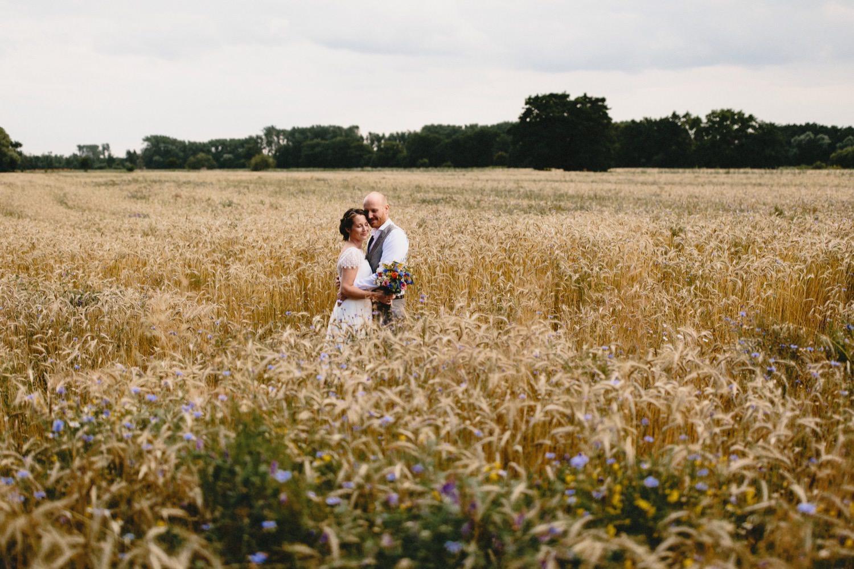 Das Brautpaar steht in mitten eines Weizenfeldes, gespickt mit Kornblumen.