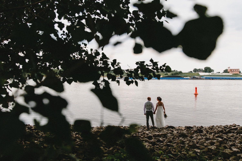 Braut und Bräutigam stehen in Kirchwerder an der Elbe und schauen sich in die Augen im Vordergrund sind Blätter und Bäume zu sehen auf der Elbe fährt ein Binnenschiff