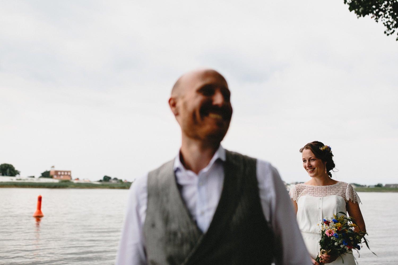 Die Braut steht hinter ihrem Bräutigam an der Elbe auf der linken Seite sieht man eine Positionsboje in Rot