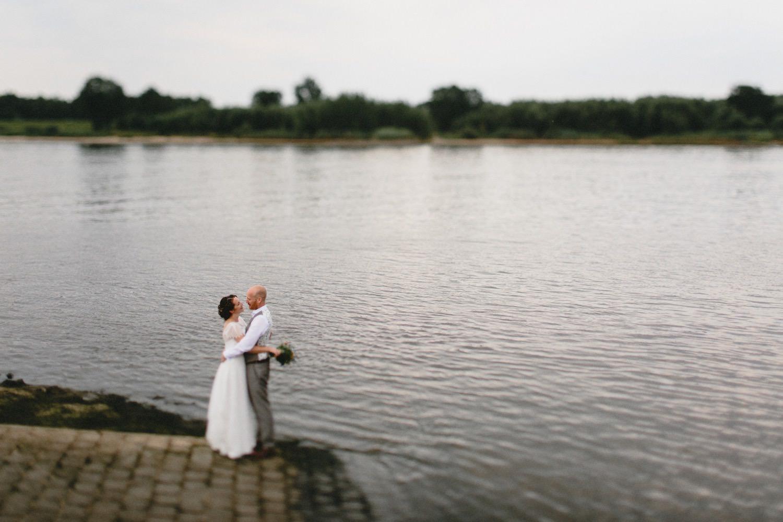 Braut und Bräutigam umarmen sich an einem Fähranleger am Zollenspieker Fährhaus
