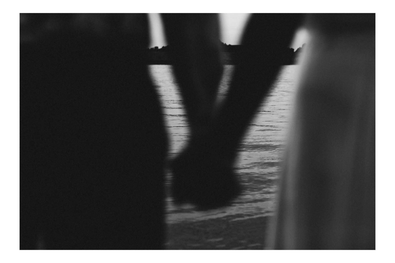 Hand in Hand stehen Braut und Bräutigam an der Elbe, das Foto ist Schwarz-Weiß und das Brautpaar ist unscharf im Vordergrund
