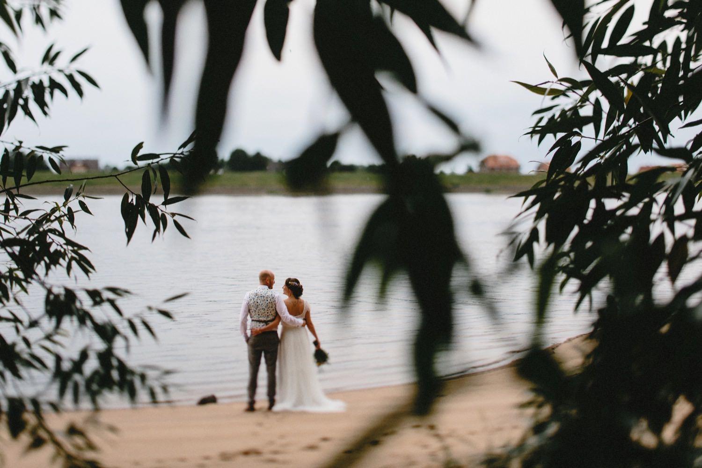 Braut und Bräutigam stehen beim Portraitshooting mit dem Hochzeitsfotografen an der Elbe in Kirchwerder in Hamburg im Vordergrund sieht man die Blätter von Bäumen