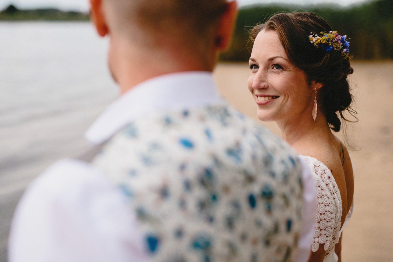 Die Braut lacht ihren Bräutigam verliebt an, sie trägt Blumenschmuck im Haar und hat ein Nasenpiercing und Ohrringe in Form von Federn und ein Brautkleid mit Spitze
