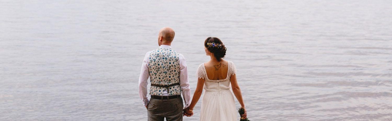 Braut und Bräutigam vor dem Wasser der Elbe, beide schauen auf das Wasser hinaus der Bräutigam trägt eine Weste von Herr von Eden mit einem Muster mit Tattoomotiven und die Braut ein Brautkleid aus Spitze