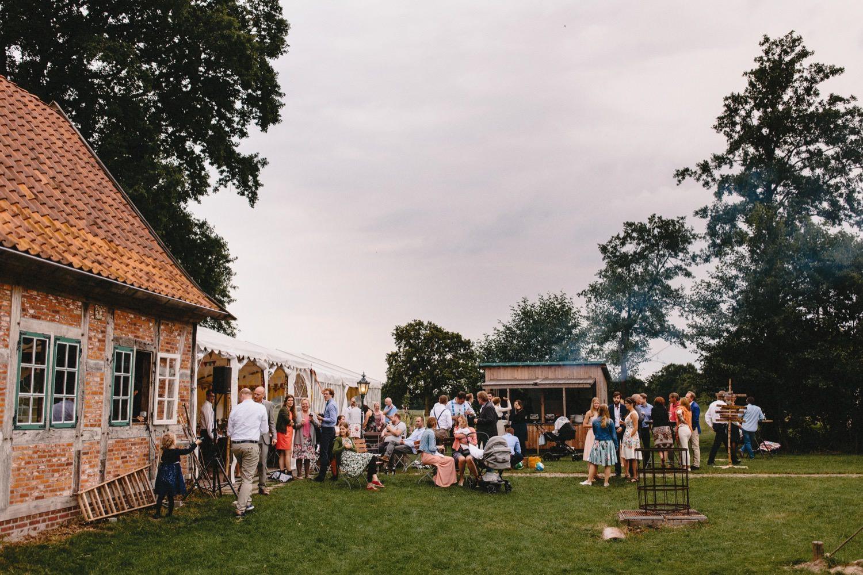 Die Gäste stehen im Abendlicht beim Empfang der Hochzeit auf Hof Eggers auf der linken Seite sieht man die Scheune für die Hochzeitsparty
