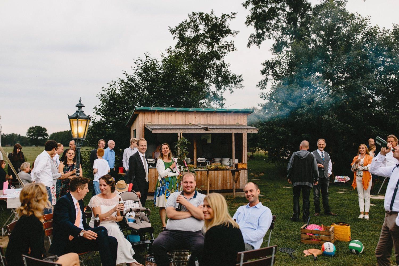 Die Hochzeitsgesellschaft auf Hof Eggers wartet dass das Essen startet, im Hintergrund sieht man den Rauch des BBQ-Buffetts