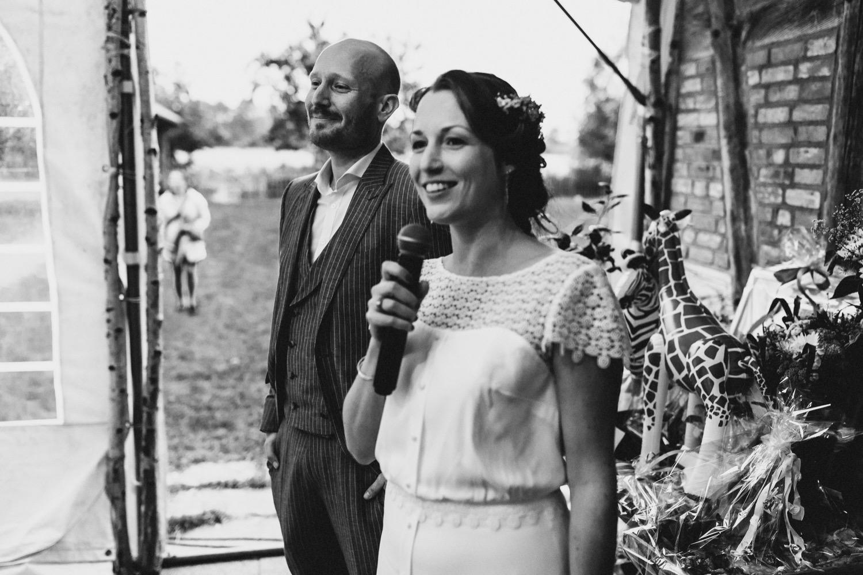 Das lachende Brautpaar bei der Hochzeitsrede vor dem Beginn des Essens