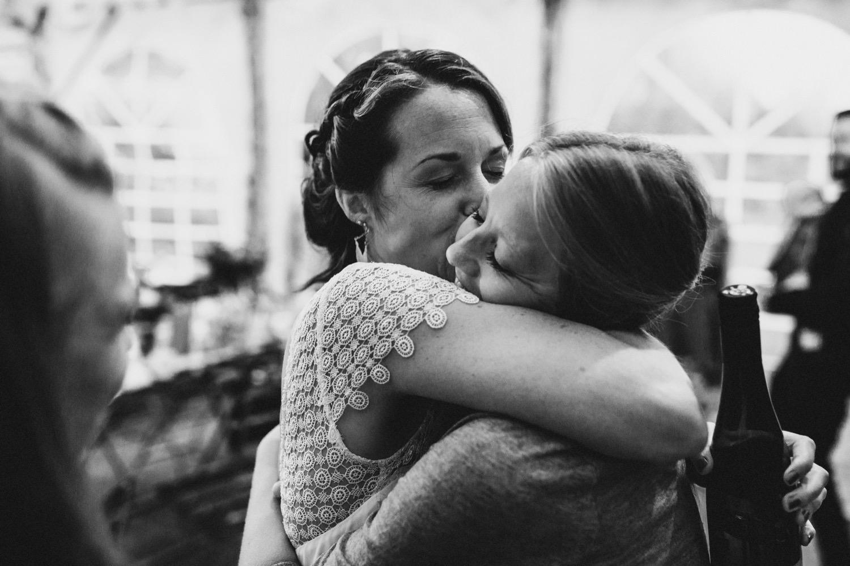 Die Braut umarmt und knutscht ihre Freundin bei der Hochzeitsparty