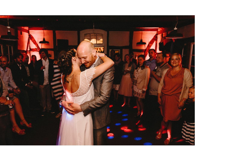 Braut und Bräutigam beim Eröffnungstanz in der Partyscheune mit Diskolicht und den Gästen um das Brautpaar herum
