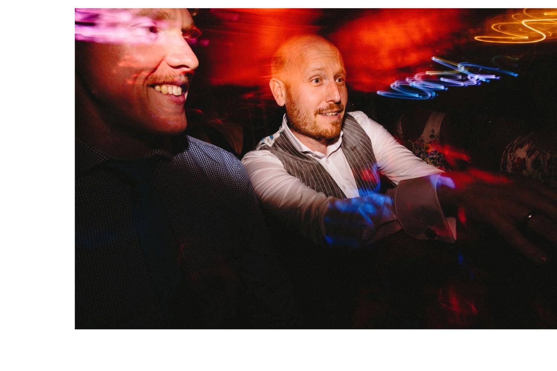 Der Bräutigam tanzt mit seinen Freunden auf der Tanzfläche, der Hochzeitsfotograf hat mit einer Langzeitbelichtung Lichteffekte in das Bild gemalt