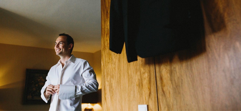 Der Bräutigam in Kiel zieht sich sein Hemd an im Vordergrund ist ein Holzschrank