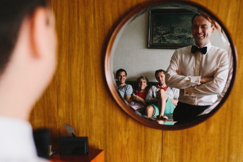 Bräutigam und seine Freunde spiegeln sich im Spiegel im Maritim Hotel in Kiel