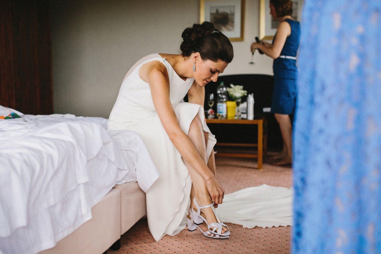 Eine Braut im weißen Kleid zieht sich ihre Schuhe an in ihrem Hotelzimmer im Maritim Hotel in Kiel