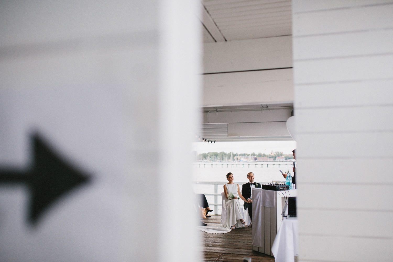 Das Brautpaar sitzt bei der Trauung in der Seebar und hört den Traurednern zu