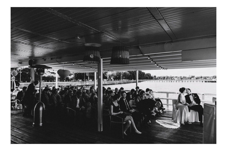 Das Küssende Brautpaar bei der Trauung in der Seebar mit den Gästen im Hintergrund