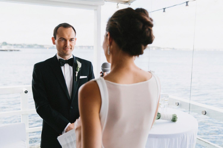 Der Bräutigam guckt seiner Braut in die Augen während sie ihm das Eheversprechen gibt. Im Hintergrund ist die Kieler Förde