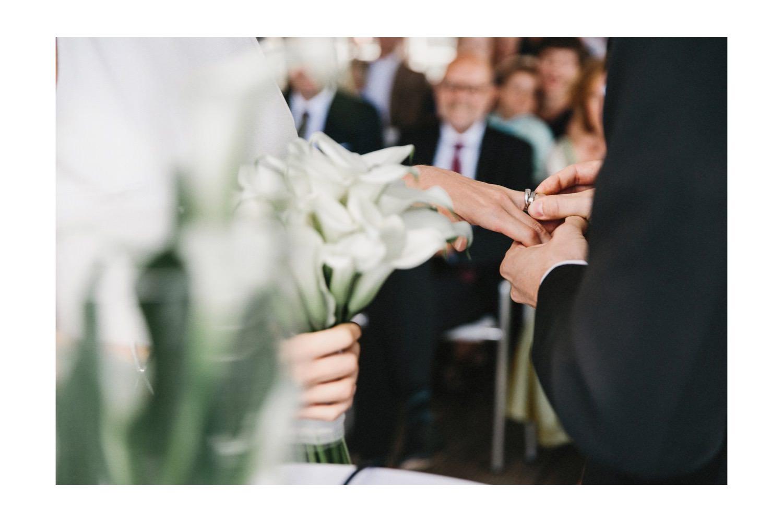 Der Bräutigam steckt seiner Braut den Ehering auf. Die Braut hält den Brautstrauß in der Hand.