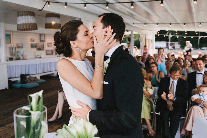 Der Erste Kuss von Braut Bräutigam nach der Trauungszeremonie in der Seebar in Kiel mit den Gästen im Hintergrund