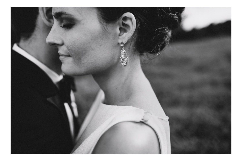 Die Braut mit Ohrring ist tief versunken in den Armen ihres Ehemannes beim Portraitshooting in Kiel mit dem Hochzeitsfotografen Till Gläser
