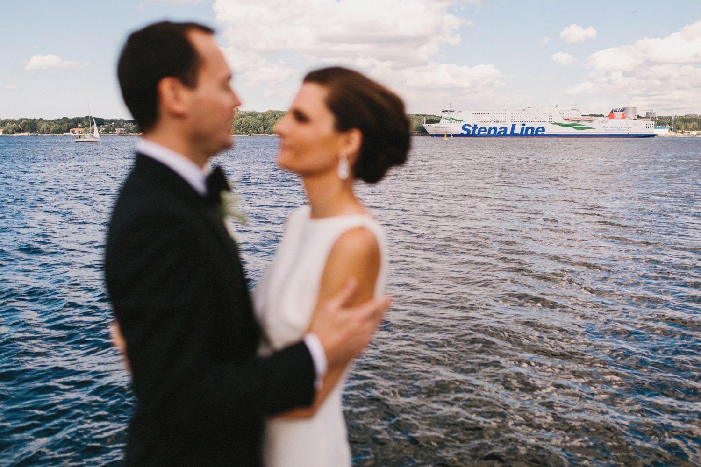 Die Eheleute stehen am Tag der Hochzeit im Brautkleid und Hochzeitsanzug an der Kieler Förde und im Hintergrund ist die Fähre zu sehen