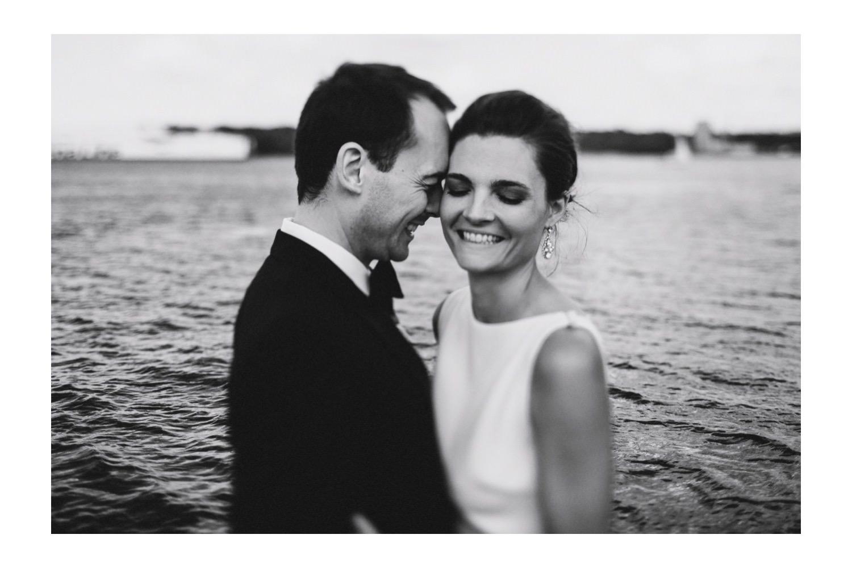 Braut und Bräutigam umarmen sich im Abendlicht an der Kieler Förde