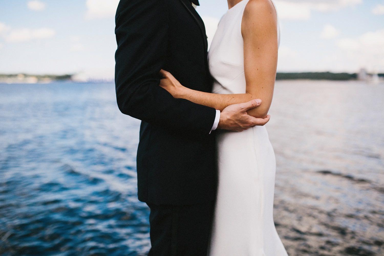 Braut und Bräutigam stehen Arm in Arm vor der Kieler Förde neben der Seebar