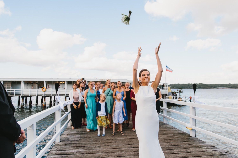 Die Braut wirft ihren Brautstrauß den unverheirateten Freundinnen auf dem Steg der seebar im Abendlicht der Kieler Förde zu