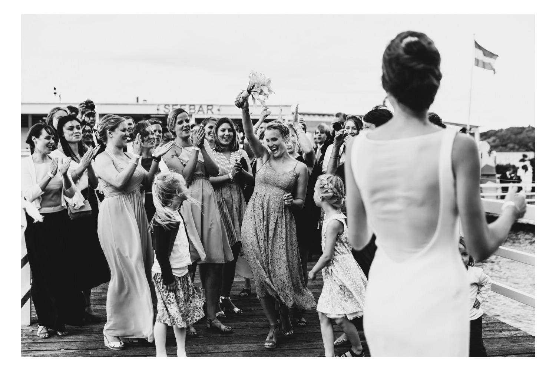 Eine Freundin der Braut hat den Brautstrauß auf der Brücke der Seebar in Kiel gefangen und freut sich
