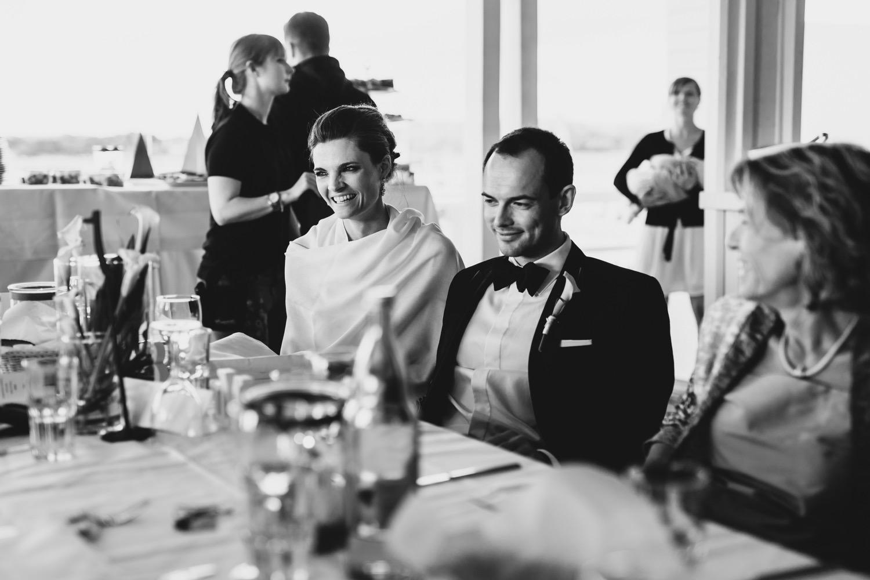 Das Brautpaar sitzt am Tisch und freut sich über über die Worde der Eltern bei der Rede