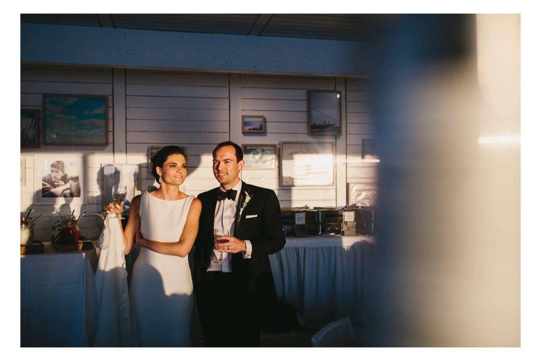 Braut und Bräutigam stehen im Sonnenuntergangslicht in der Seebar und blicken auf die Kieler Förde