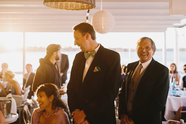 Die Hochzeitsgäste stehen im Sonnenuntergangslicht in der Seebar in Kiel