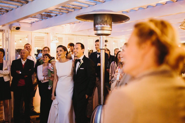 Hochzeitspaar und Gäste lachen über die gezeigte Slideshow in der Seebar